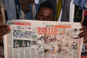 An AJWS grantee in Uganda shields his face with a tabloid article that revealed the names and faces of LGBTI advocates to incite public hatred. Some of them fear violence from homophobic extremists.