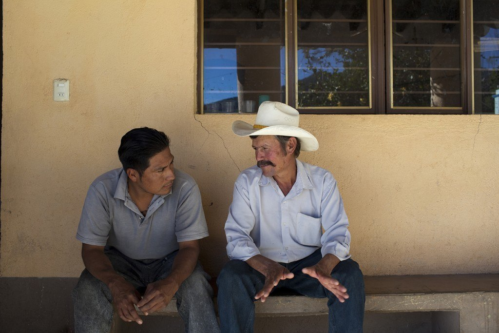 Armando de la Cruz (left), a lawyer working with Colectivo Oaxaqueño, speaks with Primo Feliciano Porras Ortiz, a villager from Maguey Largo, about the events that led to the death of Bernardo Vasquez Sanchez. Photo by Evan Abramson