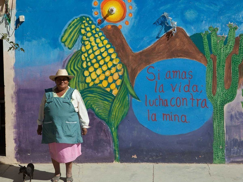 "Rufina Sanchez, the mother of murdered anti-mine activist Bernardo Vasquez Sanchez, stands in front of a mural outside her home. The mural reads: ""If you love life, fight the mine."" Photo by Evan Abramson"