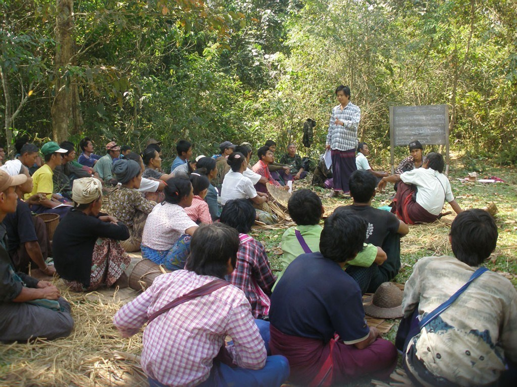 A KESAN staff member talks with farmers about their land rights. Photograph courtesy of KESAN.