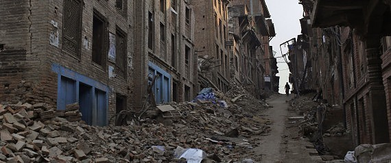 A Nepalese man walks through a path cleared with rubbles of damaged houses one month after the deadly 7.8 magnitude earthquake in Kathmandu, Nepal Monday, May 25, 2015. Two powerful earthquakes devastated Nepal on April 25 and May 12, killing nearly 8,700 people and injuring 16,800 others. The quakes and aftershocks also triggered many landslides in the Himalayan nation, which boasts eight of the world's highest mountains gets about half a million tourists every year, with many coming to trek the Himalayan nation's scenic mountain trails. (AP Photo/Niranjan Shrestha)