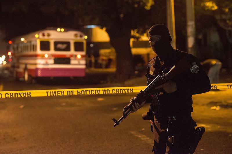 A police officer stands guard after the murder of a bus driver in San Salvador. By Encarni Pindado for NPR