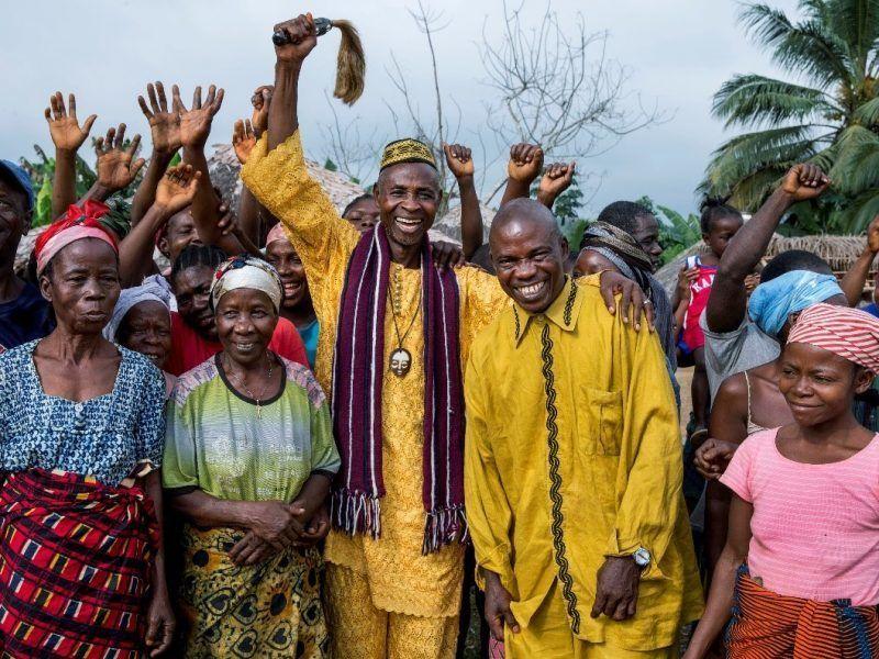Pictured are members of Liberia's Jogbahn clan, who saved their village from an attempted land grab with help from AJWS grantee Sustainable Development Institute (SDI). SDI helped 11 towns in Grand Bassa County, Liberia, push back on a British-owned palm oil company attempting to grab their land to extend their plantation. The fight took years, but the villagers eventually prevailed. AJWS continues to support SDI in Liberia to promote justice and ensure the rights of local people are protected and respected. SDI is fighting against illegal logging, social and economic injustices, weak law enforcement, poor accountability, abuse of community rights, and land grabbing in Liberia. SDI works to ensure that the benefits from natural resources are equitably distributed by improving the implementation of land laws governing the rights of forest communities. Photograph by Jonathan Torgovnik.