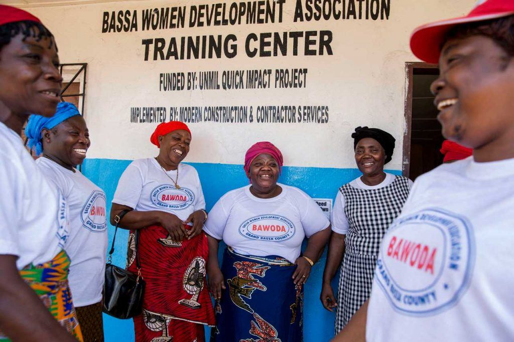 Martha Karnga and her staff share a laugh outside BAWODA's headquarters in Buchanan, Grand Bassa County.