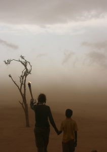 Mia Farrow walking with a child into a dust storm in Chad. Photograph by Ruth W. Messinger
