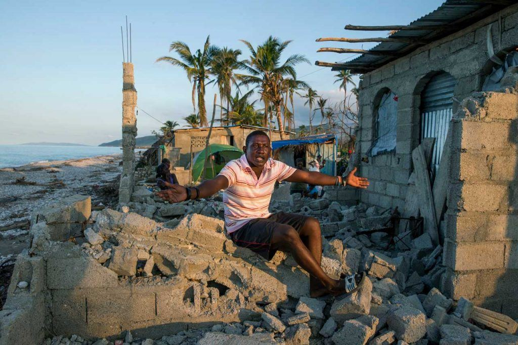 A man named Cidieu Jean Baptiste throws up his arms in frustration while sitting on top of the pile of rubble that used to be his home, which is very close to the ocean.
