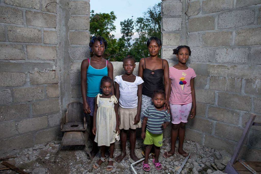 Francoise Inocent stands with her 5 children in a concrete structure without a roof- it is their home. That, along with all of their belongings, was destroyed in the Hurricane.
