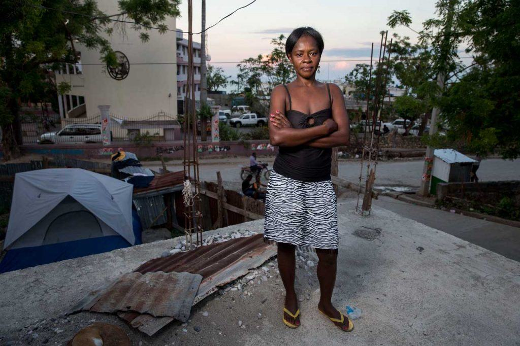 Françoise Inocent wearing a skirt and tank top with her arms crossed, standing at the site of what remains of her damaged home in Jérémie following Hurricane Matthew. Her home has a foundation but no roof or walls. There is a tent inside.