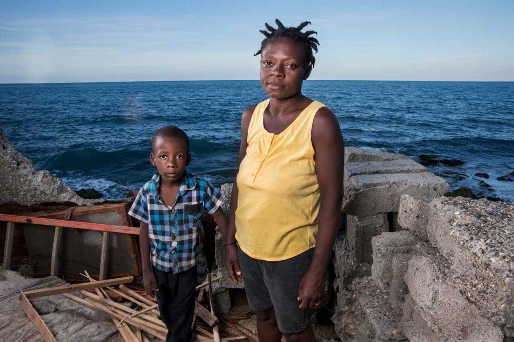 Gertie Mathurin standing with her young son Moise Henri wear serious expressions at the site of their damaged home in Jérémie. The walls and roof of the home are gone, and it is right on the coast. Gertie has received support from AJWS grantee SOFA. Photograph by Jonathan Torgovnik