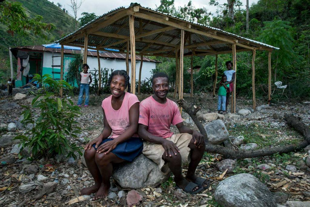 Perlage St.-Rose and Nico Aseau sit outside on some rocks near their home with a new tin roof, thanks to BDHH.