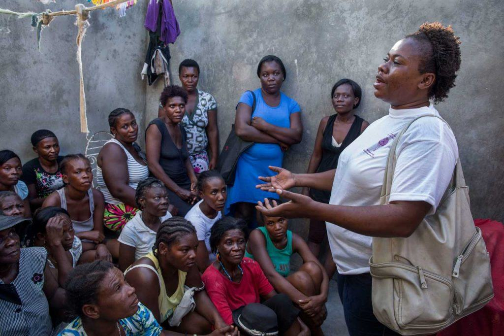 SOFA representative Neslie François stands in front of a group of women, facilitating a meeting about women's empowerment with community members in Jérémie. Photograph by Jonathan Torgovnik
