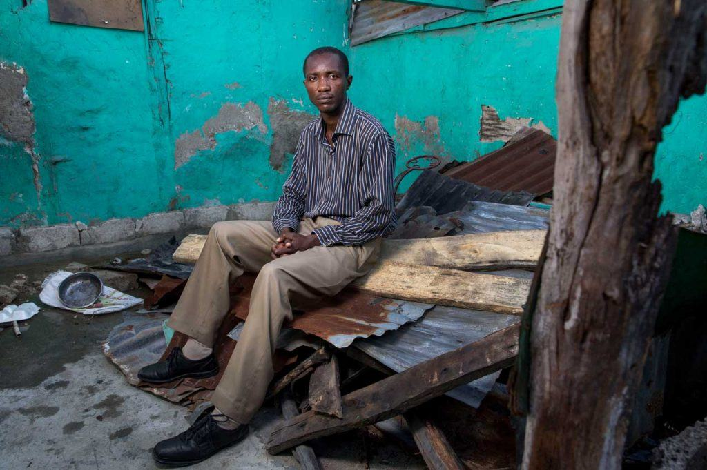 Vernace Denis sits on top of the fallen roof inside of his home that was damaged by Hurricane Matthew in Les Cayes.