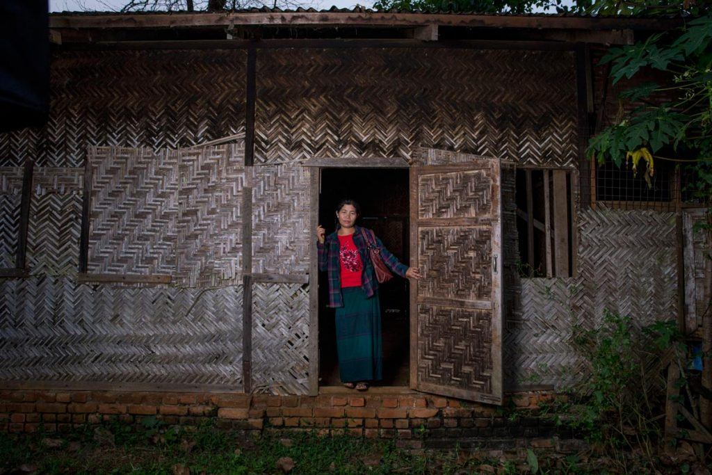 Ja Hkawn at the site of her old home and store, which she was forced to abandon and is now in ruins.
