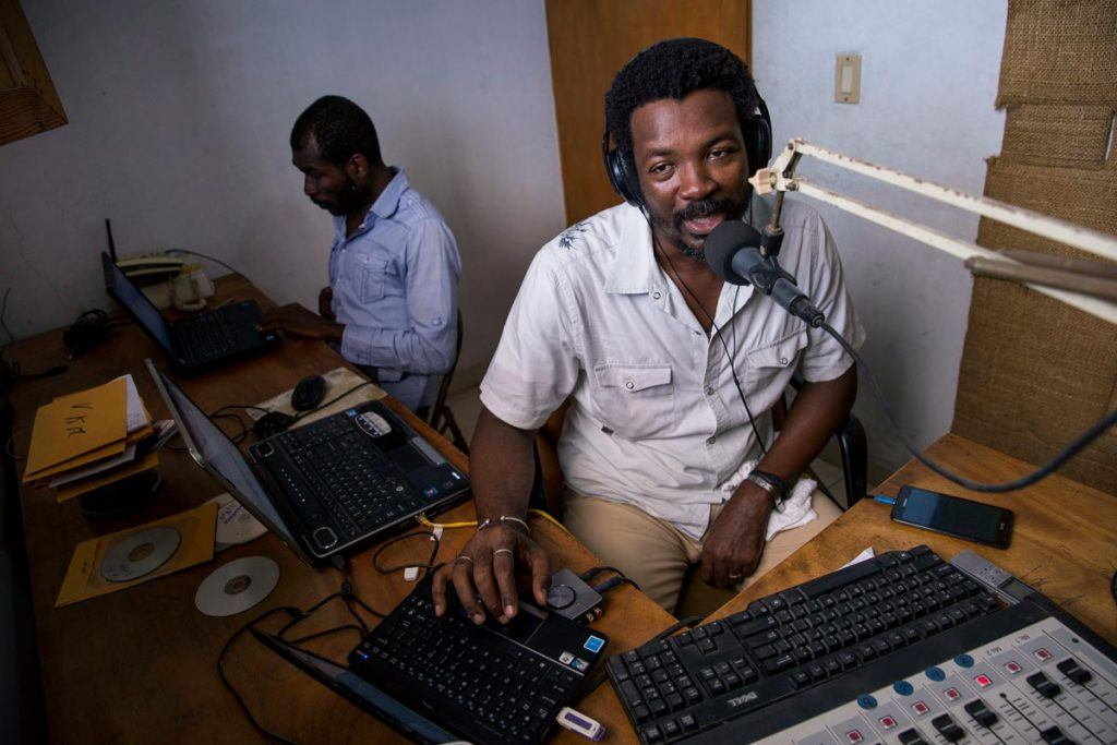 Radyo VKM's Max-Imbert Marcelin (speaking into a radio microphone) and Claude Charles (sitting at a laptop in the back) are using the airwaves to support recovery efforts in Haiti's Southern Department following Hurricane Matthew. Photo by Jonathan Torgovnik