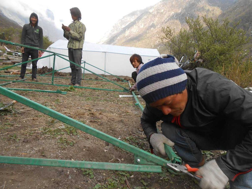 Members of AJWS grantee HCC constructing greenhouses in the arid Langtang Valley that feed dozens of families. Photo by HCC.