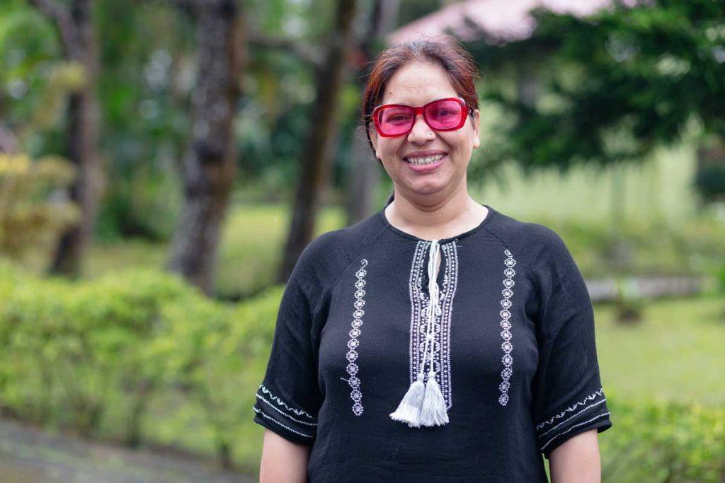 Radhika Sapkota of Sahayatri Samaj has been helping women who have experienced violence attain justice in Nepal. Here, she faces the camera wearing pink sunglasses and smiling. Photo by Ben Beringuela