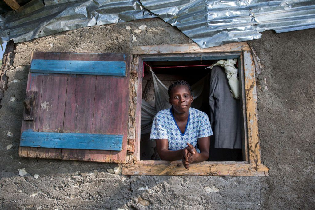 Tèt Kole member Marie Yolene Dossous, leaning out the window of a home with a tin roof, is helping Haiti's rural poor get back on their feet. Photo by Jonathan Torgovnik