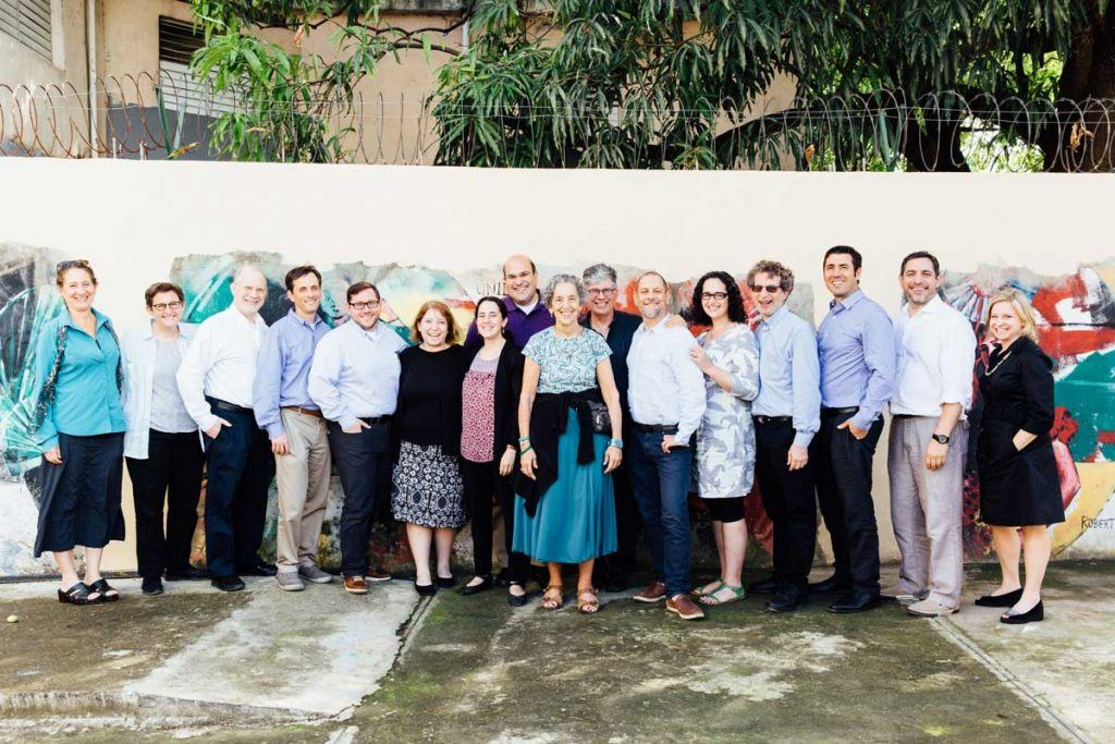 The 15 Global Justice Fellows standing in front of a wall with a mural. AJWS Global Ambassador Ruth Messinger is front and center. The rabbis and cantors are smiling. Photo by Christine Han Photography.