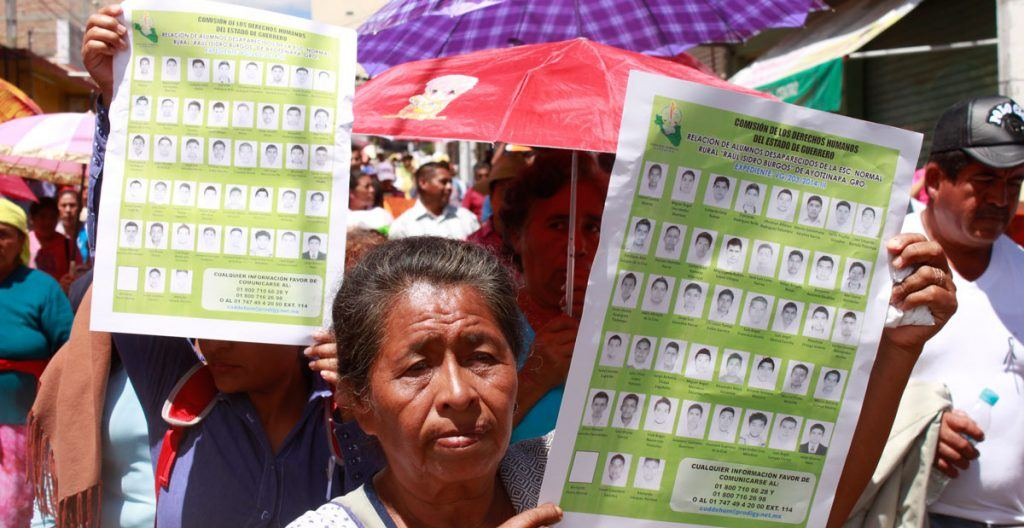 A woman holding a sign with photos of the 43 missing students.
