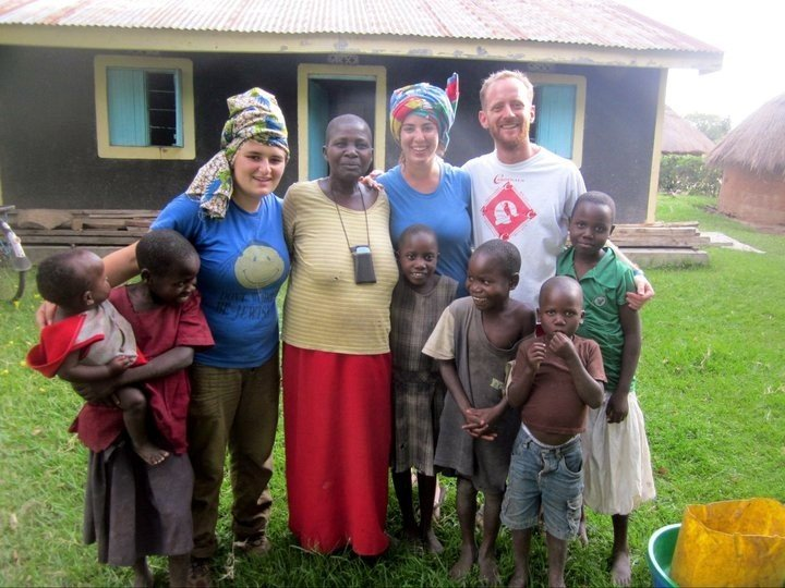 Josh (back row, 2nd from right) with participants and a local family on Volunteer Summer 2011 in Uganda.