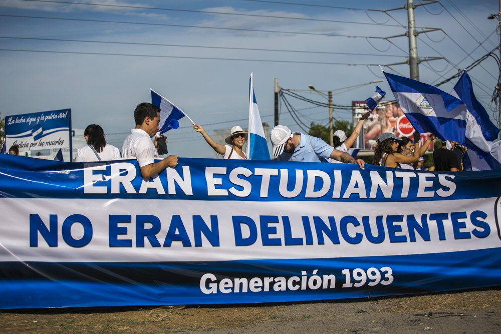 "Protesters carry a sign that reads ""They were students, not delinquents."" Photo by Jorge Mejia Peralta."