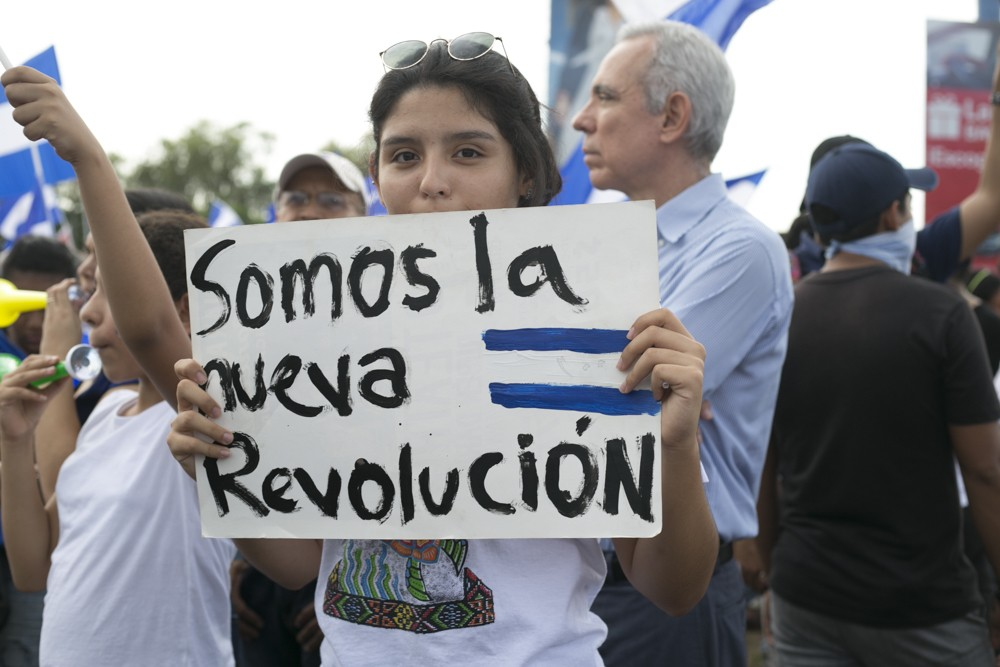 "A young protester in a crowd carries a sign that reads ""We are the new revolution."" Photo by Jorge Mejia Peralta."