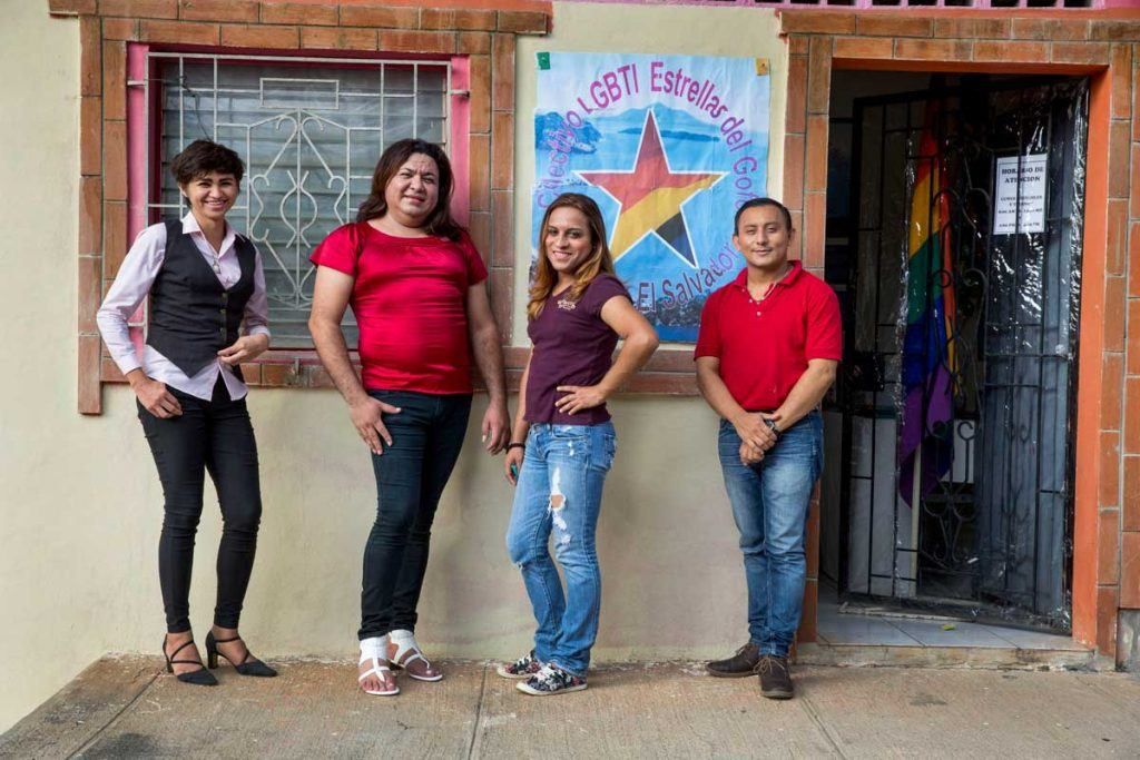 Four leaders of Estrellas del Golfo smile and pose outside their office in La Union, El Salvador. There is a large sign with a rainbow star and the name of their organization on the wall. Photo by Jonathan Torgovnik