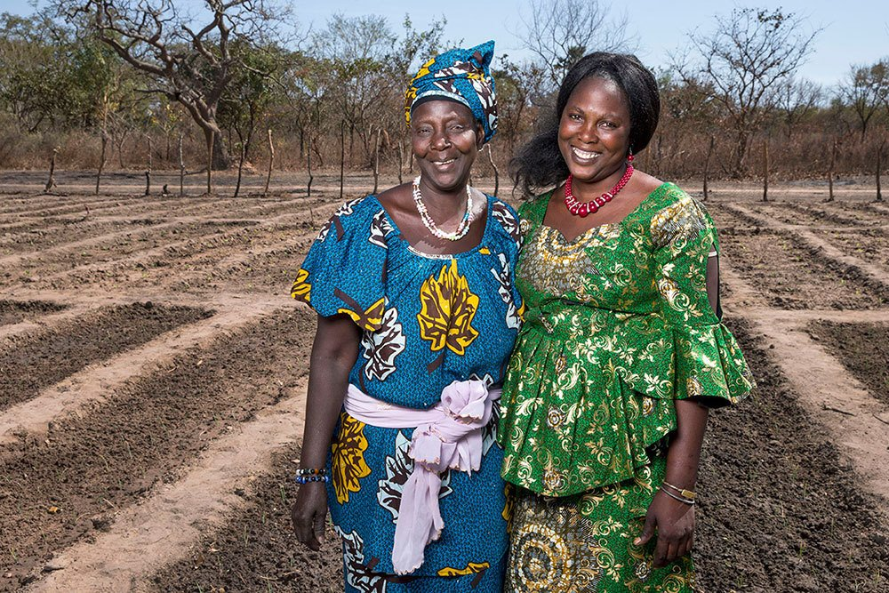 Neighbors Awa Djiba (wearing a green dress) and Mama Jamma (wearing a blue dress) stand in their garden together. Photo by Jonathan Torgovnik